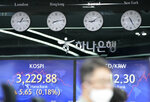 A currency trader watches computer monitors near the screens showing the Korea Composite Stock Price Index (KOSPI), left, and the foreign exchange rate between U.S. dollar and South Korean won at the foreign exchange dealing room in Seoul, South Korea, Thursday, June 3, 2021. Shares have advanced in Asia Thursday after a day of modest gains on Wall Street led by buying of energy and technology stocks. Oil prices also rose. (AP Photo/Lee Jin-man)