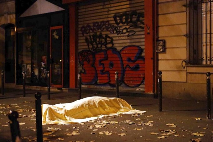 FILE - In this Friday Nov. 13, 2015 file photo a victim under a blanket lays dead outside the Bataclan theater in Paris. (AP Photo/Jerome Delay, File)