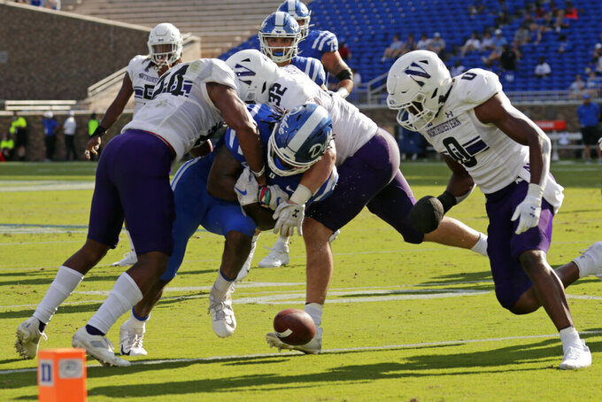 Duke running back Mataeo Durant (21) fumbles as he is hit by Northwestern defensive back Rod Heard II (24), linebacker Bryce Gallagher (32) and defensive back Coco Azema (0) during the first half of an NCAA college football game in Durham, N.C., Saturday, Sept. 18, 2021. (AP Photo/Chris Seward)