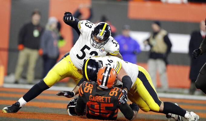 Cleveland Browns defensive end Myles Garrett (95) is punched by Pittsburgh Steelers center Maurkice Pouncey (53) and tackled by offensive guard David DeCastro (66) during the second half of an NFL football game, Thursday, Nov. 14, 2019, in Cleveland. (AP Photo/Ron Schwane)