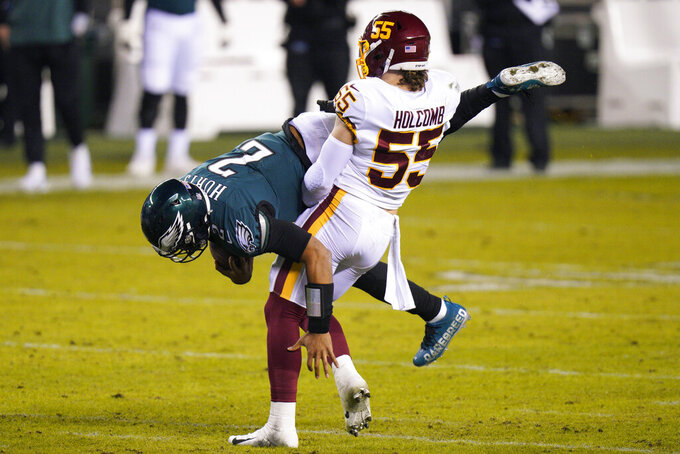 Washington Football Team's Cole Holcomb (55) tackles Philadelphia Eagles' Jalen Hurts (2) during the first half of an NFL football game, Sunday, Jan. 3, 2021, in Philadelphia. (AP Photo/Chris Szagola)