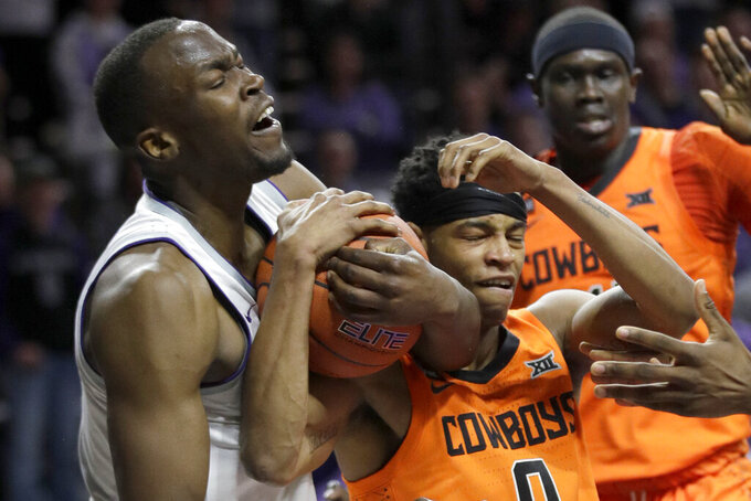 Kansas State forward Makol Mawien, left, is tied up with Oklahoma State guard Avery Anderson III (0) during the second half of an NCAA college basketball game in Manhattan, Kan., Tuesday, Feb. 11, 2020. Oklahoma State defeated Kansas State 64-59. (AP Photo/Orlin Wagner)
