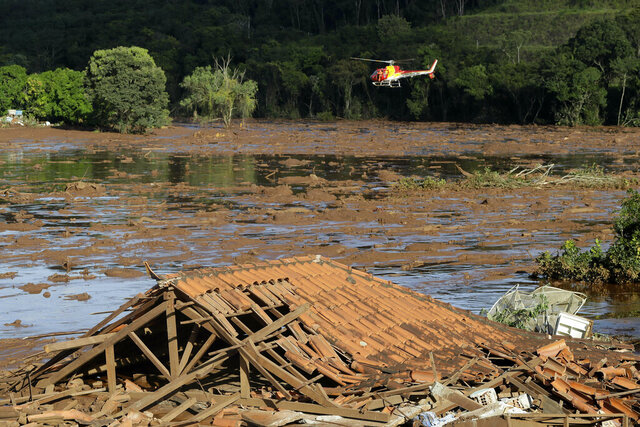 FILE - In this Sunday, Jan. 27, 2019 file photo, rescue workers in a helicopter search a flooded area after a dam collapsed in Brumadinho, Brazil. Prosecutors in the Brazilian state of Minas Gerais said Tuesday, Jan. 21, 2020 they will present charges against mining giant Vale, its German auditor Tuv Sud and 16 individuals in connection with the dam collapse last January that killed more than 200 people. (AP Photo/Andre Penner, File)
