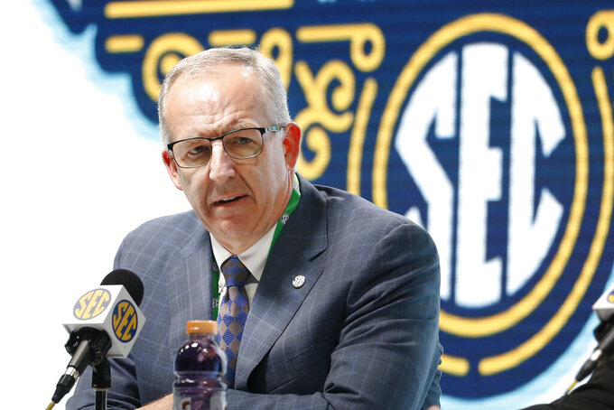 FILE - In this March 11, 2020, file photo, Southeastern Conference Commissioner Greg Sankey announces that fans will not be allowed in the arena to watch NCAA college basketball games in the SEC tournament in Nashville, Tenn. The SEC came into this college football season with a contingency plan to deal with coronavirus-related issues. While those plans have been severely tested as the pandemic has wreaked havoc, Southeastern Conference officials continue adapting to navigate setbacks in their pursuit of a league title and possible national championship. (AP Photo/Mark Humphrey, File)
