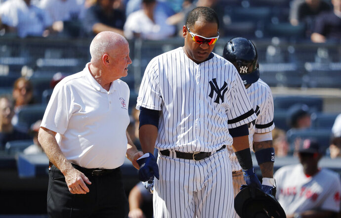 FILE - In this Aug. 3, 2019, file photo, New York Yankees' Edwin Encarnacion is helped by trainer Steve Donohue after being hit by a pitch thrown by Boston Red Sox's Josh Smith during the eighth inning of a baseball game in New York. Encarnacion suffered a broken right wrist. Donahue has been promoted to the newly created role of director of medical services for the Yankees. The 63-year-old, starting his 42nd year with the team, had been head athletic trainer for eight seasons after working from 1986-2011 as assistant athletic trainer to Gene Monahan. (AP Photo/Michael Owens, File)