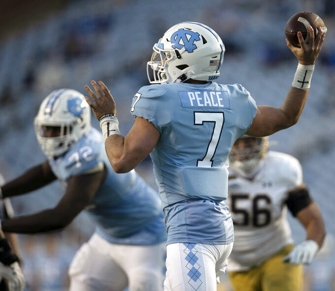 """North Carolina quarterback Sam Howell (7), who has the word """"Peace""""  as his nameplate, throws a pass against Notre Dame during an NCAA college football game, Friday, Nov. 27, 2020, at Kenan Stadium in Chapel Hill, N.C. (Robert Willett/The News & Observer via AP)"""