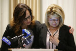 As Patty Fortney-Julius, left, offers support, her sister Lara Fortney McKeever cries as she speaks to reporters during a news conference in Newark, N.J., Monday, Dec. 2, 2019. The two sisters from Pennsylvania are suing the Archdiocese of Newark and the Diocese of Harrisburg, Pennsylvania. They allege clergy in Newark knew a priest had sexually abused children before he moved to Harrisburg and abused them and their sisters for years. Lawsuits alleging sexual abuse by Roman Catholic clergy are taking center stage in New Jersey as the state's relaxation of statute of limitations rules takes effect. (AP Photo/Seth Wenig)