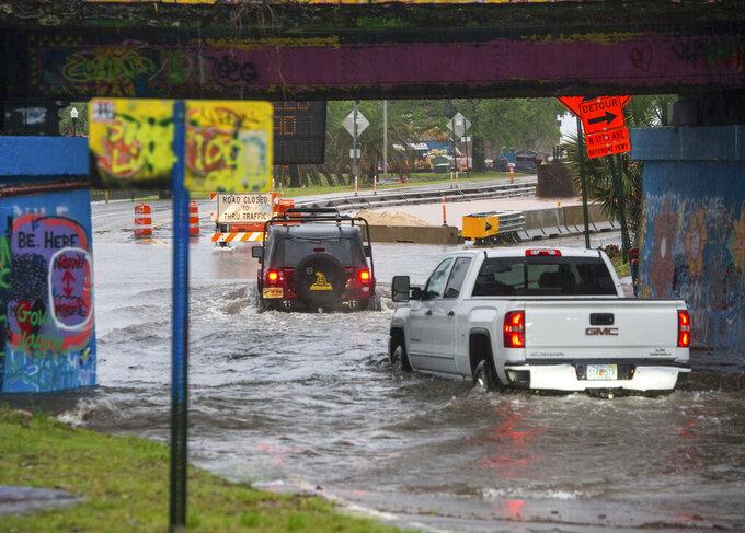 Trucks make their way through high water Saturday, April 10, 2021, at the Graffiti Bridge in Pensacola, Fla., after a powerful storm swept through the area.   (John Blackie/Pensacola News Journal via AP)