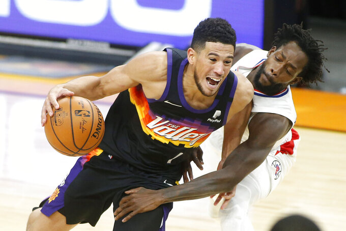 Phoenix Suns guard Devin Booker (1) drives as Los Angeles Clippers guard Patrick Beverley defends during the second half of an NBA basketball game Sunday, Jan. 3, 2021, in Phoenix. (AP Photo/Ralph Freso)