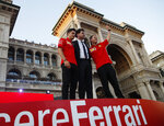From left, Charles Leclerc, team principal Mattia Binotto, and Sebastian Vettel salute Ferrari fans as they attend an event to celebrate the 90th anniversary of the foundation, at Milan's Duomo square, Italy, Wednesday, Sept. 4, 2019. The F1 GP of Italy will take place at Monza race track, near Milan, Sunday. (AP Photo/Antonio Calanni)