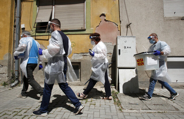 Members of a special election team with a ballot box and voting material make their way visiting voters who have tested positive for COVID-19 or are in self-isolation, in Skopje, North Macedonia, Monday, July 13, 2020. North Macedonia holds its first parliamentary election under its new country name this week, with voters heading to the polls during an alarming spike of coronavirus cases in the small Balkan nation. Opinion polls in the run-up to Wednesday's vote indicate a close race between coalitions led by the Social Democrats and the center-right opposition VMRO-DPMNE party. (AP Photo/Boris Grdanoski)