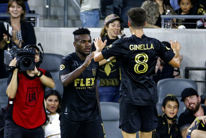 Los Angeles FC midfielder Jose Cifuentes, left, celebrates his goal with Francisco Ginella (8) during the second half of the team's MLS soccer match against the Vancouver Whitecaps in Los Angeles, Saturday, July 24, 2021. The game ended in a 2-2 draw. (AP Photo/Ringo H.W. Chiu)
