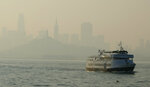 A ferry boat makes its way toward Alcatraz Island as the skyline in the background is obscured by wildfire smoke and haze Monday, Nov. 12, 2018, in San Francisco. (AP Photo/Eric Risberg)