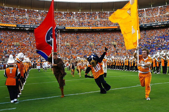 FILE — In this Sept. 22, 2018, file photo, Tennessee cheerleaders run onto the field at Neyland Stadium before an NCAA college football game between Tennessee and Florida in Knoxville, Tenn. Tennessee's athletic budget for 2020-21 assumes the Volunteers will have fans in the stands for football season but still includes a $10.1 million cut in overall revenues. (AP Photo/Wade Payne, File)