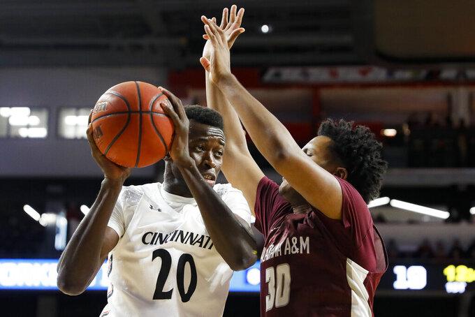 Cincinnati's Mamoudou Diarra (20) looks to pass as Alabama A&M's Brandon Houston (30) defends during the first half of an NCAA college basketball game Thursday, Nov. 14, 2019, in Cincinnati. (AP Photo/John Minchillo)