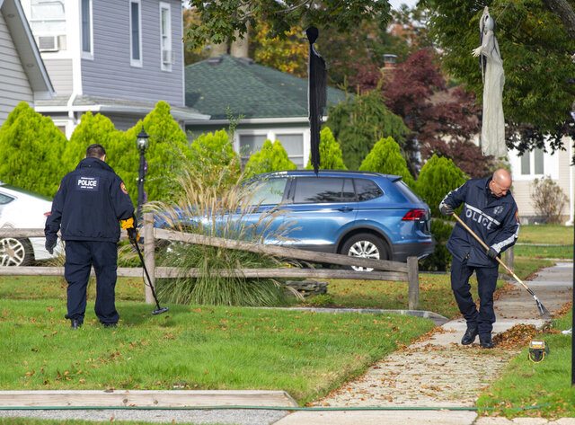 In this Oct. 25, 2019, photo, Nassau County Police look for evidence outside of a Seaford, N.Y., home where off-duty New York City Police Sgt. Justin Ellis shot personal trainer Patrick Catania during an altercation. On Wednesday, Nov. 25, 2020, both men were arraigned on charges related to the incident. (Howard Schnapp/Newsday via AP)
