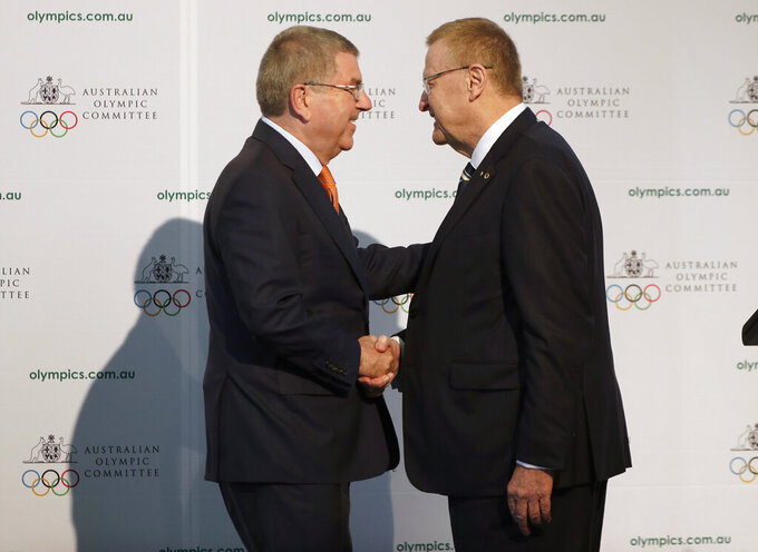 "FILE - In this Saturday, May 4, 2019 file photo, International Olympic Committee President Thomas Bach, left, shakes hands with Australian Olympic Committee (AOC) President John Coates at the AOC annual general meeting in Sydney, Australia.  The Australian Olympic bid is on a fast-track to host the 2032 Olympics Wednesday Feb. 24, 2021, after the International Olympic Committee executive board gave Queensland ""preferred bidder"" status, 11 years ahead of the games.(AP Photo/Rick Rycroft, File)"