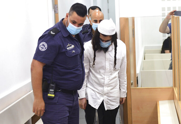 FILE - In this May 18, 2020 file photo, Israeli Jewish extremist Amiram Ben-Uliel arrives at a district court for a verdict in Lod, Israel. On Monday, Sept. 14, 2020, an Israeli court handed down three life sentences to Ben-Uliel convicted in a 2015 arson attack that killed a Palestinian toddler and his parents. The Lod District Court found the Jewish settler guilty of murder in May for the killing of 18-month-old Ali Dawabsheh by firebombing his home in the West Bank village of Duma. (Avshalom Sassoni/Pool Photo via AP, File)