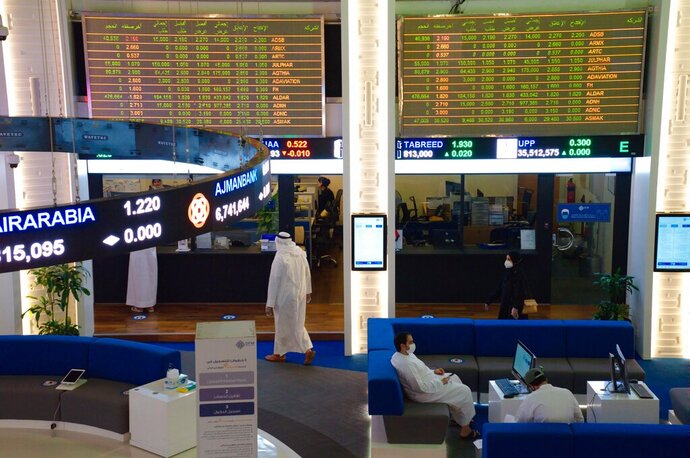 Emiratis wearing face masks due to the coronavirus pandemic work on the floor of the Dubai Financial Market in Dubai, United Arab Emirates, Tuesday, July 7, 2020. Dubai reopened its Dubai Financial Market stock exchange Tuesday after closing its floor due to the coronavirus pandemic. (AP Photo/Jon Gambrell)