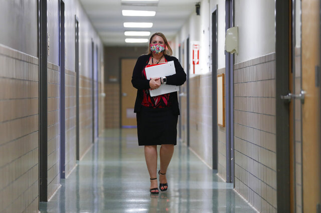 Jennifer Gottschalk, environmental health supervisor of the Toledo-Lucas County Health Department, walks down a hallway of the department's offices in Toledo, Ohio, on Wednesday, June 24, 2020. When the coronavirus pandemic struck earlier in the year, the county's department was so short-staffed that her duties included overseeing campground and pool inspections, rodent control and sewage programs, while also supervising outbreak preparedness for a community of more than 425,000 people. (AP Photo/Paul Sancya)