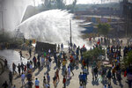 Policemen use water cannon to prevent protesting farmers from moving ahead towards Delhi, at the border between Delhi and Haryana state, Friday, Nov. 27, 2020. Thousands of agitating farmers in India faced tear gas and baton charge from police on Friday after they resumed their march to the capital against new farming laws that they fear will give more power to corporations and reduce their earnings. While trying to march towards New Delhi, the farmers, using their tractors, cleared concrete blockades, walls of shipping containers and horizontally parked trucks after police had set them up as barricades and dug trenches on highways to block roads leading to the capital. (AP Photo)