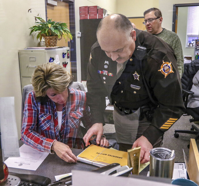 In This Wednesday, Jan. 9, 2019 photo, Deputy County Clerk Tonya Payne, left, and Major Barry Smith, chief deputy with the Daviess County Sheriff's Department, document the 17 absentee ballots that were rejected by the county board of elections during the November 2018 election before releasing them for transfer to Frankfort. A Republican-dominated board of Kentucky lawmakers is investigating a Democrat's election by a one-vote margin. (Greg Eans/The Messenger-Inquirer via AP)