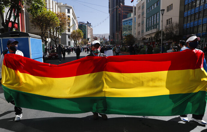 Public transport drivers take part in a protest demanding an increase in fares because quarantine measures to curb the spread of the new coronavirus have decreased their income, in La Paz, Bolivia, Wednesday, July 1, 2020. (AP Photo/Juan Karita)