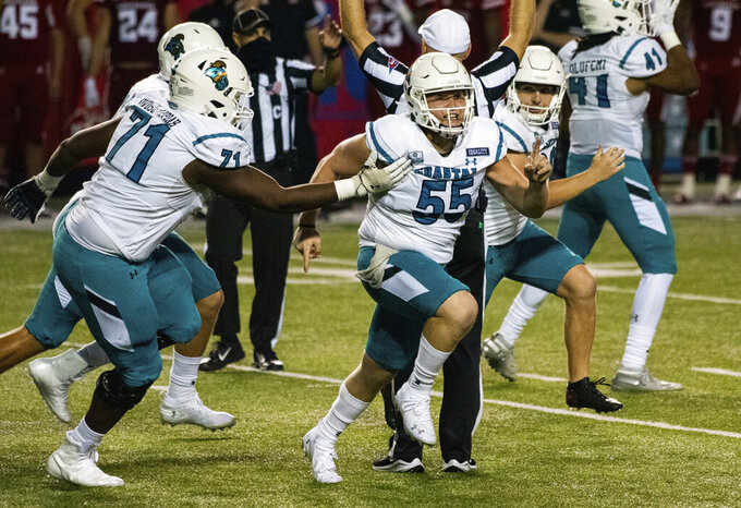 Coastal Carolina players celebrate after place kicker Massimo Biscardi (29) kicked the go-ahead and eventual game-winning field goal during the second half of an NCAA college football game against Louisiana-Lafayette in Lafayette, La., Wednesday, Oct. 14, 2020. (AP Photo/Paul Kieu)
