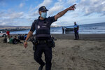 A Police officer react to the media as migrants from Morocco sit on a beach after arriving at the coast of the Canary Island, crossing the Atlantic Ocean sailing on a wooden boat on Tuesday, Oct.20, 2020.  Some 1,000 migrants have spent the night again sleeping in emergency tents in a dock while authorities in the Canary Islands complain that the Spanish government keeps blocking transfers of newly arrived migrants to the mainland over coronavirus concerns. (AP Photo/Javier Bauluz)