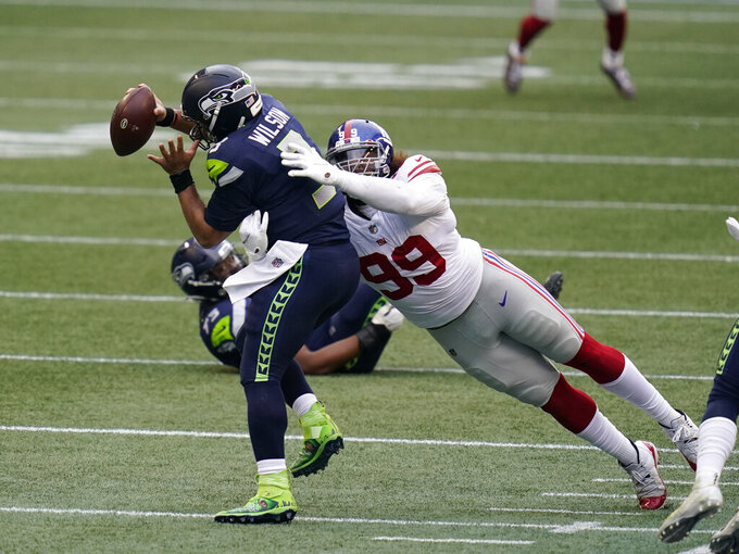 Seattle Seahawks quarterback Russell Wilson (3) is sacked by New York Giants defensive end Leonard Williams (99) during the first half of an NFL football game, Sunday, Dec. 6, 2020, in Seattle. (AP Photo/Elaine Thompson)