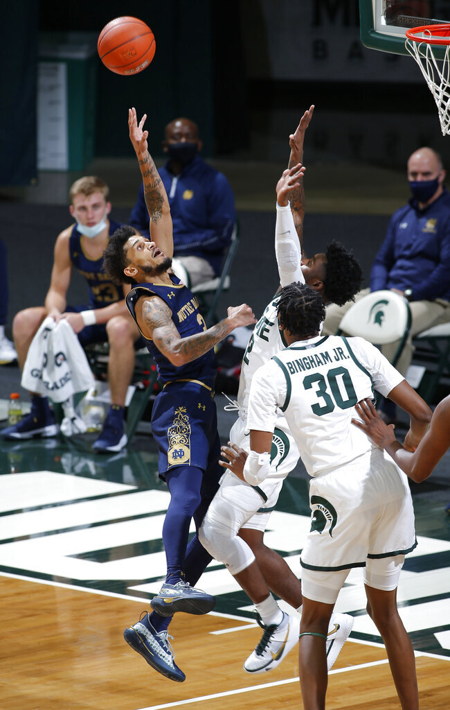 Notre Dame's Prentiss Hubb, left, shoots against Michigan State's Rocket Watts and Marcus Bingham Jr. (30) during the second half of an NCAA college basketball game Saturday, Nov. 28, 2020, in East Lansing, Mich. Michigan State won 80-70. (AP Photo/Al Goldis)