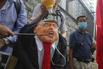 Pro-China supporters hit the effigy of U.S. President Donald Trump outside the U.S. Consulate during a protest in Hong Kong, Saturday, May 30, 2020. President Donald Trump has announced a series of measures aimed at China as a rift between the two countries grows. He said Friday that he would withdraw funding from the World Health Organization, end Hong Kong's special trade status and suspend visas of Chinese graduate students suspected of conducting research on behalf of their government. (AP Photo/Kin Cheung)