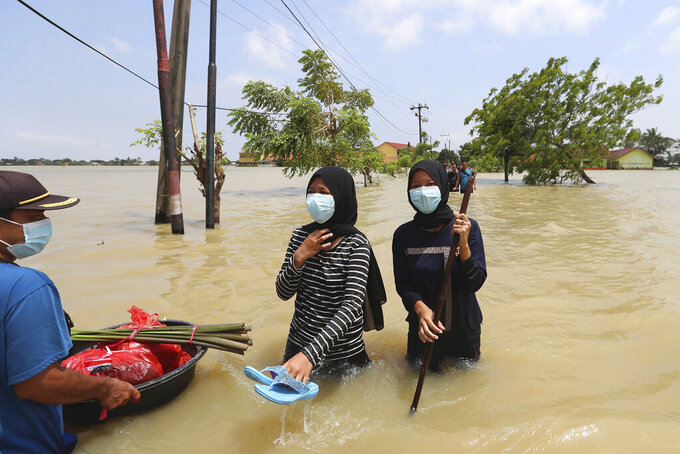 Indonesians carry their belongings as they wade through the water in a flooded neighborhood following heavy rains in Bekasi, Indonesia, Monday, Feb. 22, 2021. Thousands of residents are being evacuated on the outskirts of Indonesia's capital amid flooding after the Citarum River embankment broke. (AP Photo/Achmad Ibrahim)