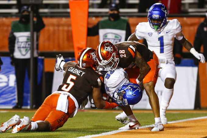 Buffalo running back Jaret Patterson (26) bulls his way into the end zone for a touchdown between Bowling Green defensive backs Sy Dabney (5) and Shon Strickland (28) during the first half of an NCAA college football game in Bowling Green, Ohio, Tuesday, Nov. 17, 2020. (Scott W. Grau/Sentinel-Tribune via AP)