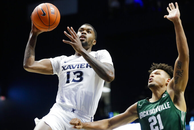 Xavier's Naji Marshall (13) shoots against Jacksonville's Derrick Flowers (21) during the second half of an NCAA college basketball game Tuesday, Nov. 5, 2019, in Cincinnati. (AP Photo/John Minchillo)