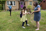 Abby Norman greets her daughters Juliet, 11, left, and Priscilla, 9, as they arrive home from school to the family's Decatur, Ga., home on Tuesday, May 18, 2021. Priscilla was in tears the first morning of testing this year because she felt pressure to do well, but didn't feel prepared after remote learning. (AP Photo/Ben Gray)