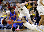 Michigan's Charles Matthews, bottom, Jon Teske (15) and Florida's Kevarrius Hayes (13) scramble for the ball during the first half of a second round men's college basketball game in the NCAA Tournament, in Des Moines, Iowa, Saturday, March 23, 2019. (AP Photo/Nati Harnik)