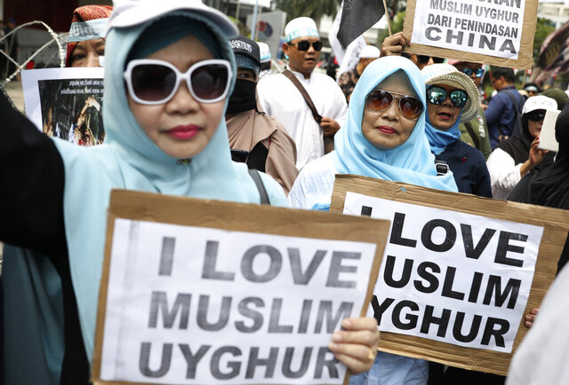 Muslim women hold posters during a rally outside the Chinese Embassy in Jakarta, Indonesia, Friday, Dec. 27, 2019. Over a thousand Muslims staged the rally calling to an end to alleged oppression against Muslim Uighur ethnic minority in China's region of Xinjiang. (AP Photo/Dita Alangkara)