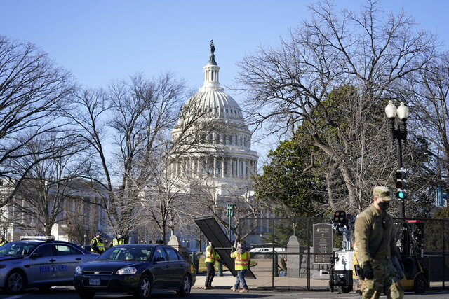 Workers install no-scale fencing around the U.S. Capitol in Washington, Thursday, Jan. 7, 2021. President-elect Joe Biden's inauguration was already going to be scaled back, but after a mob stormed the U.S. Capitol, ransacking the building and triggering chaos that stretched all the way to the Senate floor, questions began to arise about whether having a presidential ceremony on the steps of the same building could also pose serous security risk. (AP Photo/Evan Vucci)