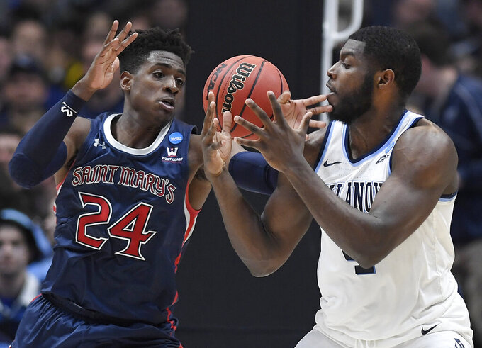 St. Mary's Malik Fitts (24) and Villanova's Eric Paschall (4) reach for the ball during the second half of a first round men's college basketball game in the NCAA tournament, Thursday, March 21, 2019, in Hartford, Conn. (AP Photo/Jessica Hill)