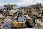 In this Tuesday, April 2, 2019, photo, a man makes his way through the ruins of houses destroyed by earthquake-triggered liquefaction at Balaroa neighborhood in Palu, Central Sulawesi, Indonesia. Though the Sept. 28, 2018, tragedy in remote central Sulawesi that killed thousands of people is fading from memory, large parts of the city look like they were struck only yesterday, a daily reminder to residents of the horrors they lived through. (AP Photo/Tatan Syuflana)