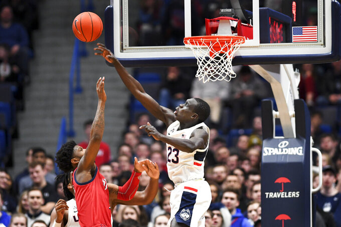 Connecticut's Akok Akok (23) blocks the shot of New Jersey Institute of Technology's San Antonio Brinson (2) in the second half of an NCAA college basketball game Sunday, Dec. 29, 2019, in Hartford, Conn. Akok had 5 blocks in the game. (AP Photo/Stephen Dunn)