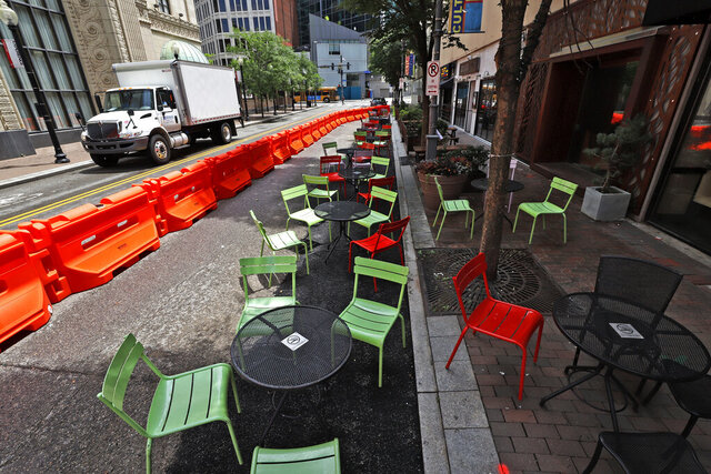 FILE - In this June 23, 2020, file photo orange barriers enclose chairs and tables that will be used for dining along Sixth Street between Liberty and Penn avenues in downtown Pittsburgh. A report by Moody's Analytics, a private sector economic research firm, released Wednesday, June 24, is warning anew of continuing damage to the economy if Washington doesn't deliver several hundred billion dollars in budget relief to states and local governments amid the coronavirus pandemic. (AP Photo/Gene J. Puskar, File)