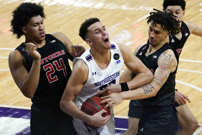 Northwestern forward Pete Nance, center, reacts as he battles for a rebound against Rutgers guard/forward Ron Harper Jr., left, and guard Caleb McConnell during the second half of an NCAA college basketball game in Evanston, Ill., Sunday, Jan. 31, 2021. (AP Photo/Nam Y. Huh)