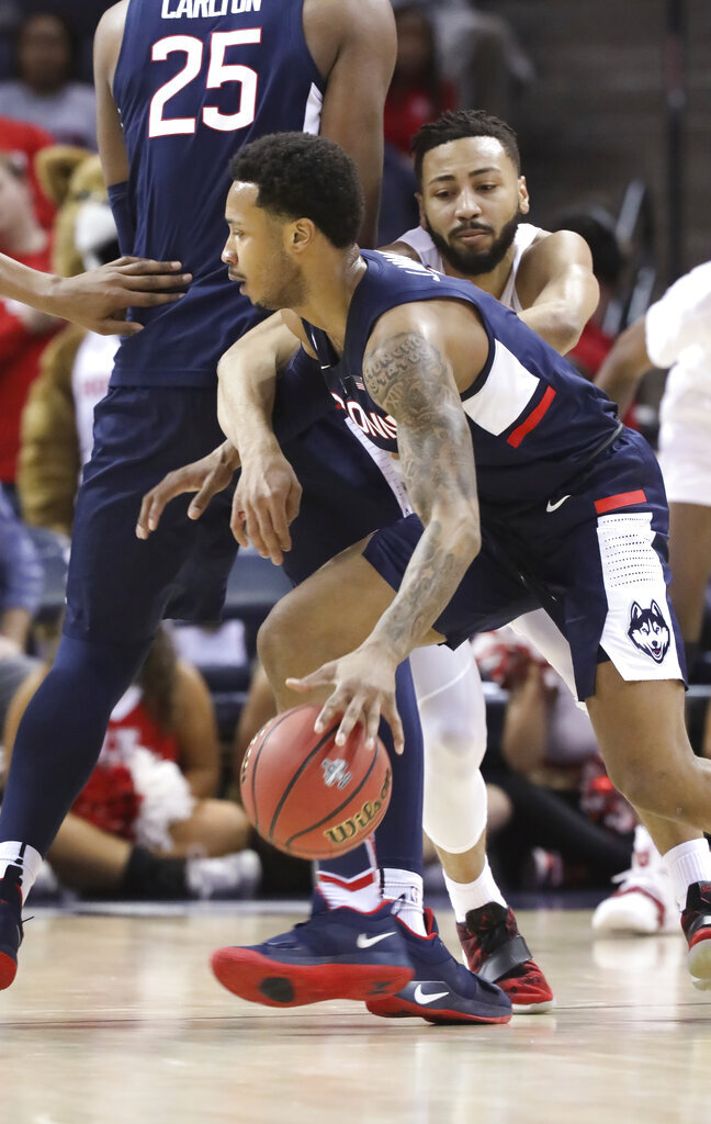 Connecticut's Jalen Adams, front, dribbles the ball as Houston's Galen Robinson during the first half of an NCAA college basketball game against Houston at the American Athletic Conference tournament Friday, March 15, 2019, in Memphis, Tenn. (AP Photo/Troy Glasgow)