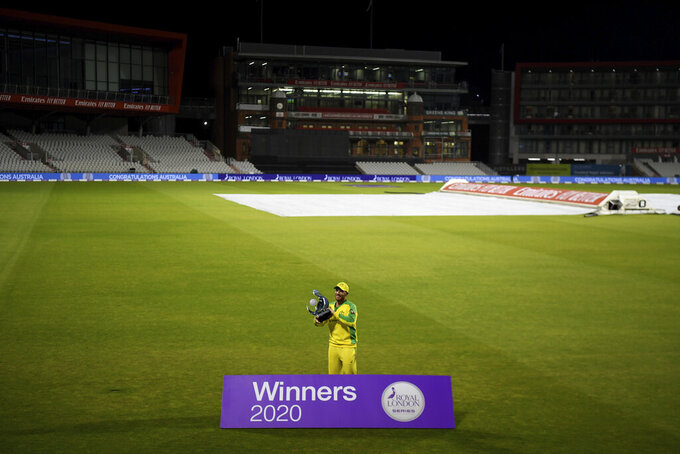 Australia's captain Aaron Finch poses with the winners trophy after their win in the third ODI cricket match between England and Australia, at Old Trafford in Manchester, England, Wednesday, Sept. 16, 2020. (Shaun Botterill/Pool via AP)
