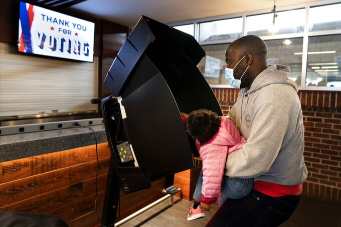 FILE - In this Oct. 27, 2020, file photo, Ron Williams, Jr., of Washington, has his daughter Mimi Williams, 2, help him to push the button while casting his vote at an early voting center at Nationals Park in Washington. Several years since its founding, BLM has evolved well beyond the initial aspirations of its early supporters. Now, its influence faces a test, as voters in the Tuesday, Nov. 3 general election choose or reject candidates who endorsed or denounced the BLM movement amid a national reckoning on race. (AP Photo/Jacquelyn Martin, File)