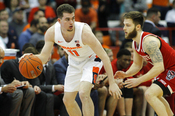 Syracuse's Joseph Girard III, left, tries to dribble past North Carolina State's Braxton Beverly, right, in the first half of an NCAA college basketball game in Syracuse, N.Y., Tuesday, Feb. 11, 2020. (AP Photo/Nick Lisi)