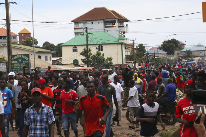 People protest on the streets of Conakry, Guinea, Thursday, Oct. 24, 2019. Some thousands of people marched Thursday in the streets of Guinea's capital protesting a bid by the president to seek another term in office.(AP Photo/Youssouf Bah)