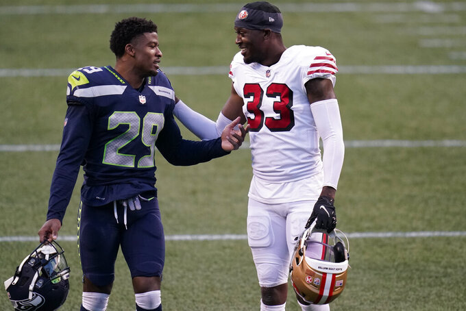 San Francisco 49ers defensive back Tarvarius Moore (33) greets Seattle Seahawks' D.J. Reed (29) after an NFL football game, Sunday, Nov. 1, 2020, in Seattle. The Seahawks won 37-27. (AP Photo/Elaine Thompson)